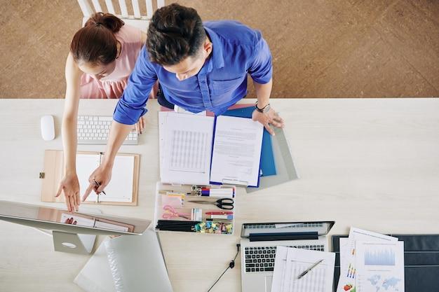 Compañeros de trabajo comparando datos financieros