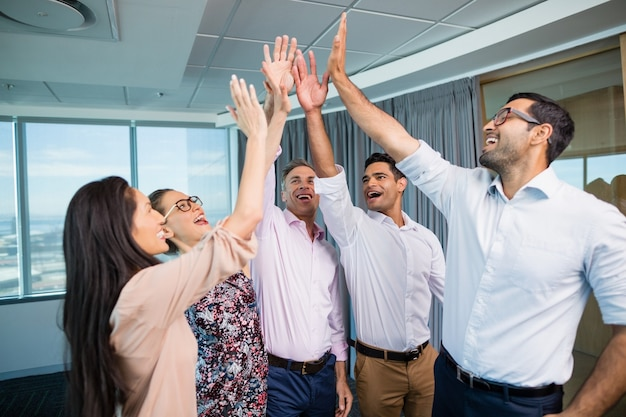 Compañeros de trabajo dando cinco durante la reunión en la oficina