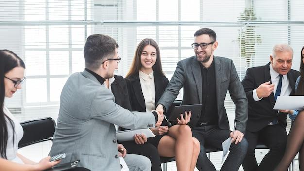 Compañeros de trabajo dándose la mano en una reunión de oficina. concepto de cooperación