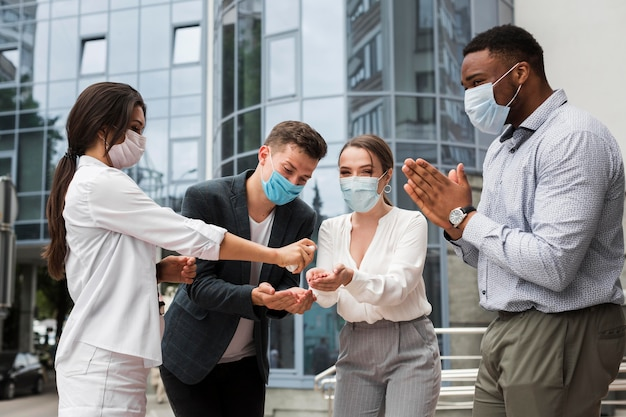 Compañeros de trabajo desinfectando las manos al aire libre durante una pandemia mientras usan máscaras