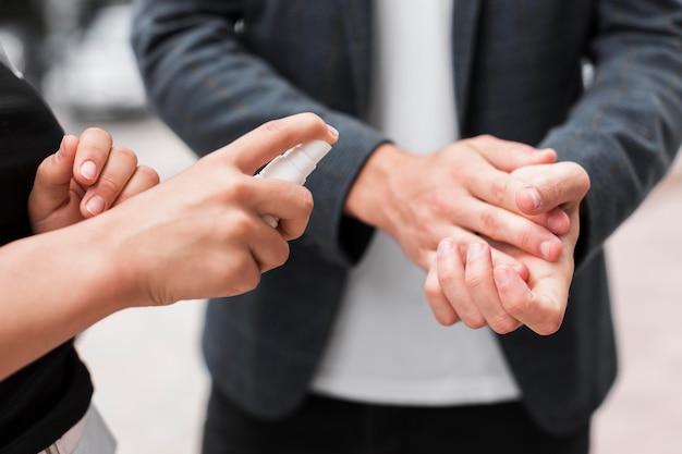 Compañeros de trabajo desinfectando sus manos al aire libre durante una pandemia