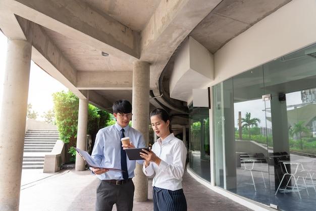 Compañeros de trabajo discutiendo cuestiones laborales al aire libre cerca del edificio de oficinas, hablando entre ellos al aire libre.