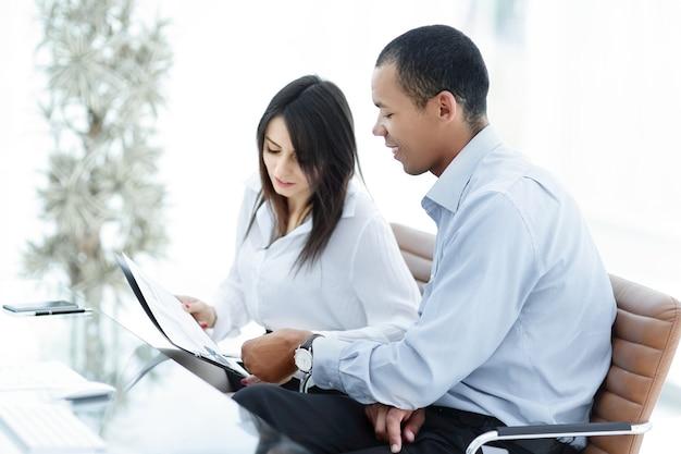 Compañeros de trabajo discutiendo documentos sentados en el escritorio