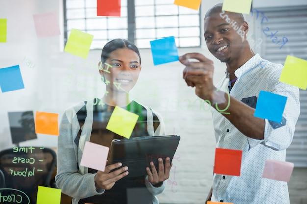 Compañeros de trabajo discutiendo sobre notas adhesivas sobre vidrio