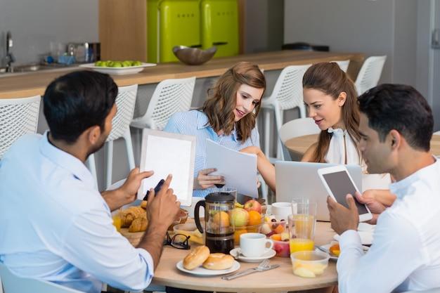 Compañeros de trabajo discutiendo sobre tableta digital mientras desayuna
