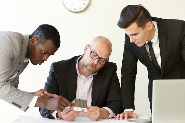 Compañeros de trabajo de la empresa constructora estimando el prototipo de la casa. hombre audaz con gafas sosteniendo un pequeño edificio de armario en las manos. afroamericano apuntando a los detalles y mirando el modelo de maqueta.