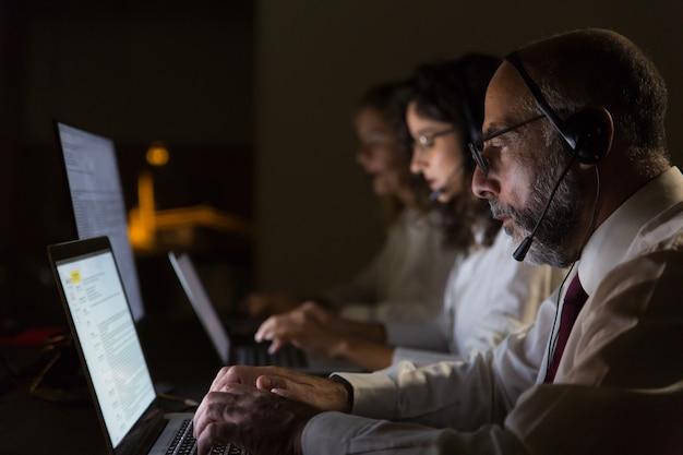 Compañeros de trabajo enfocados en auriculares escribiendo en computadoras portátiles