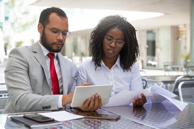 Compañeros de trabajo enfocados revisando informes
