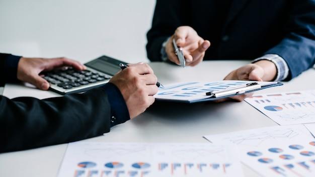 Compañeros de trabajo están discutiendo información financiera en colaboración en la oficina.