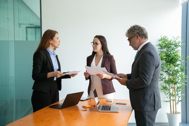 Compañeros de trabajo exitosos hablando, sosteniendo papeles y trabajando juntos