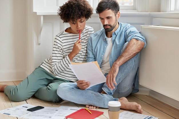 Compañeros de trabajo exitosos interraciales concentrados trabajan juntos en el informe económico anual