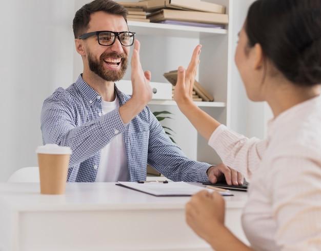Compañeros de trabajo felices celebrando con choca esos cinco