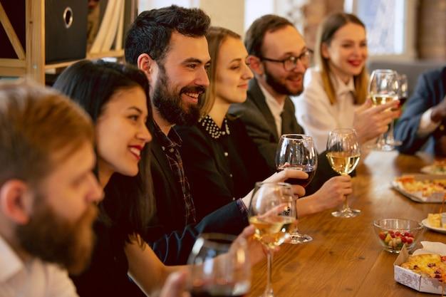 Compañeros de trabajo felices celebrando mientras la fiesta de la empresa y el evento corporativo. jóvenes caucásicos en traje de negocios animando, riendo. concepto de cultura de oficina, trabajo en equipo, amistad, vacaciones, fin de semana.