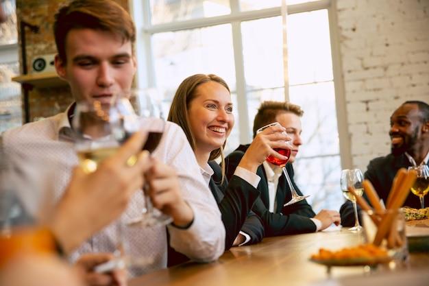 Compañeros de trabajo felices celebrando mientras la fiesta de la empresa, evento corporativo. jóvenes caucásicos en traje de negocios hablando, bebiendo vino.