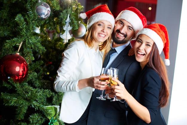 Compañeros de trabajo felices con champán celebrando la navidad