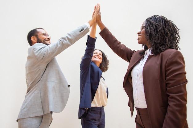 Compañeros de trabajo felices disfrutando del éxito del equipo