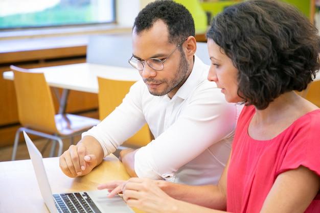 Compañeros de trabajo haciendo investigación en biblioteca