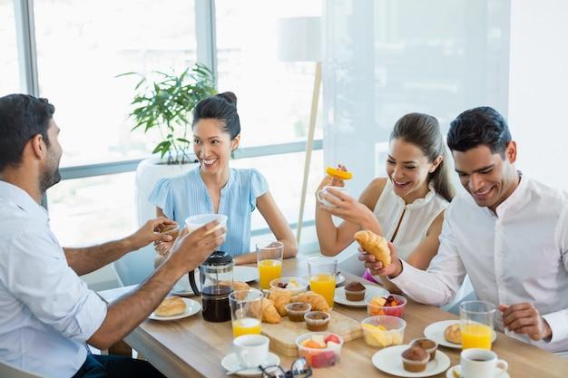 Compañeros de trabajo interactuando entre sí mientras desayunan