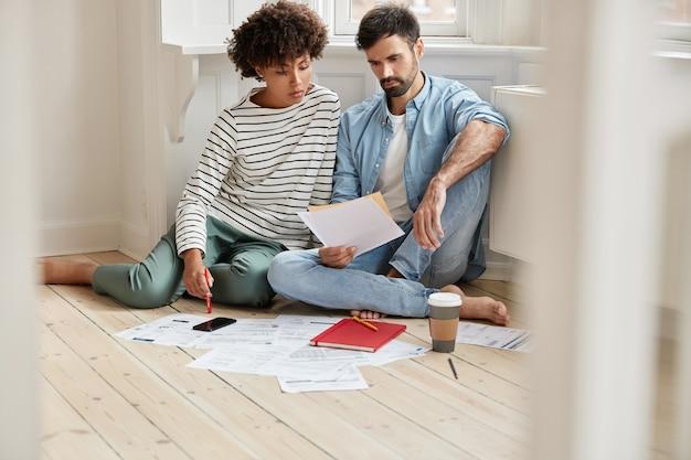 Compañeros de trabajo interraciales leen la solicitud por escrito para producir más bienes, estudian el precio de reventa y se sientan juntos en el piso de su casa
