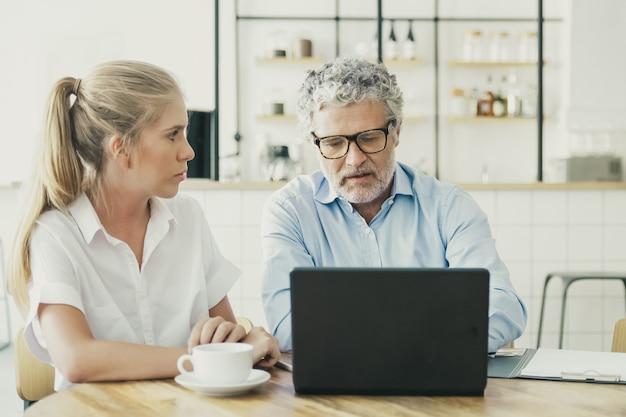 Compañeros de trabajo jóvenes y maduros reunidos en co-working, sentados en la computadora portátil abierta