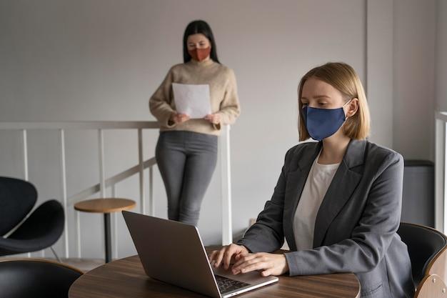 Compañeros de trabajo con máscaras médicas trabajando