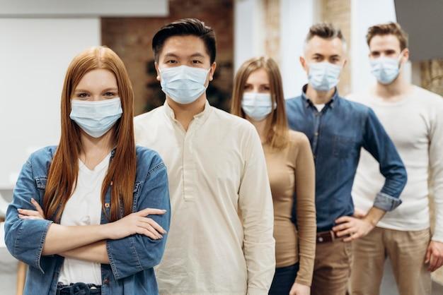 Compañeros de trabajo con máscaras médicas en el trabajo
