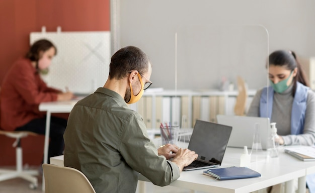 Compañeros de trabajo con mascarilla en la oficina