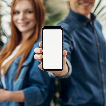 Compañeros de trabajo mostrando un teléfono de pantalla vacía