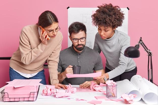 Compañeros de trabajo multiculturales concentrados en la planificación del proyecto centrado en el papel obtienen asesoramiento de un socio experimentado a través de un teléfono inteligente discuten los detalles en la mesa de reuniones crean planes redactan juntos