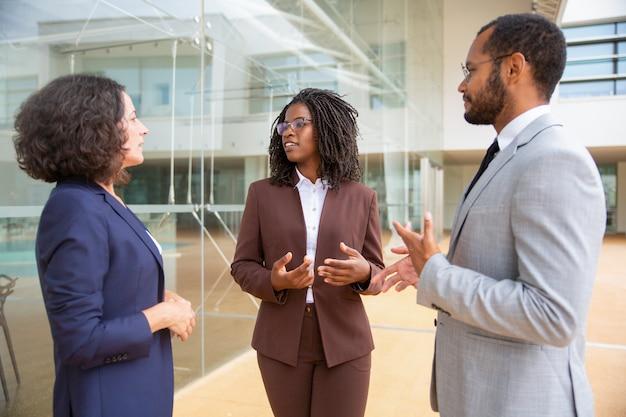 Compañeros de trabajo multiétnicos de pie y hablando