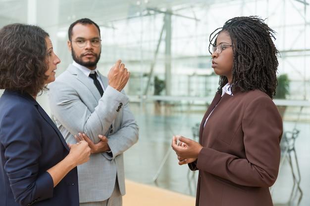 Compañeros de trabajo multiétnicos serios discutiendo proyecto afuera