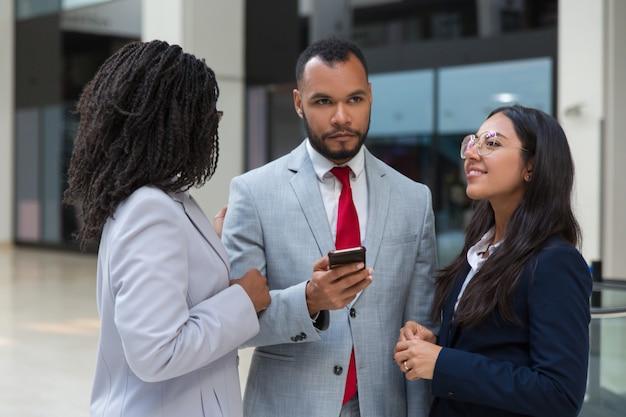 Compañeros de trabajo multiétnicos con teléfono inteligente