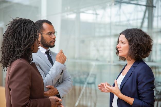 Compañeros de trabajo multirraciales hablando