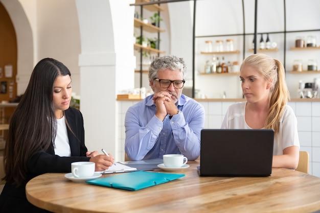 Compañeros de trabajo o socios reunidos en el trabajo conjunto, leyendo el acuerdo, usando la computadora portátil