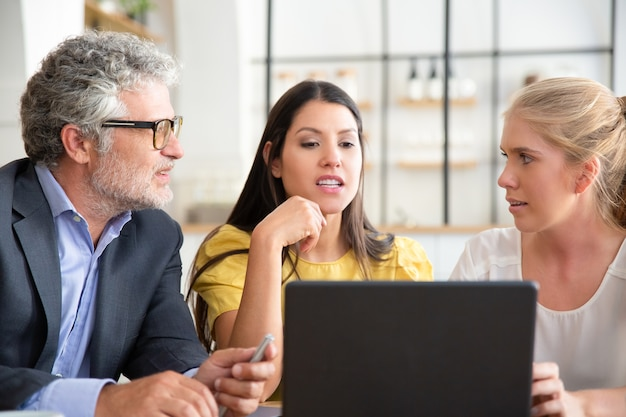 Compañeros de trabajo o socios viendo contenido en una computadora portátil y discutiendo el proyecto
