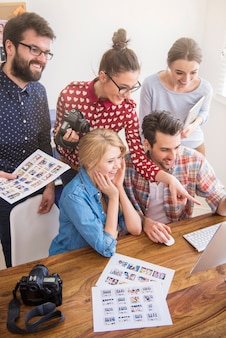Compañeros de trabajo en la oficina con cámaras fotográficas y una computadora