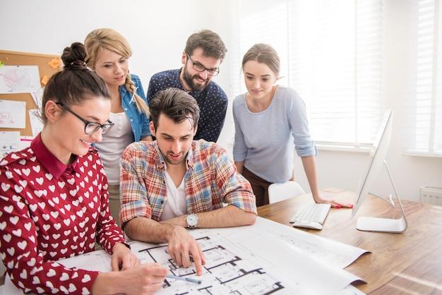 Compañeros de trabajo en la oficina con planos de arquitectura y una computadora