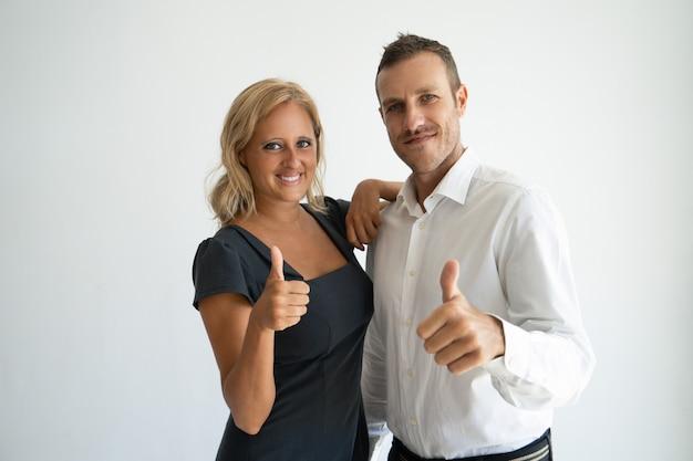 Compañeros de trabajo optimistas que muestran el pulgar hacia arriba expresando su aprobación.