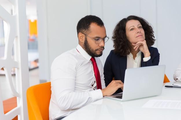 Compañeros de trabajo pensativos enfocados trabajando juntos en el proyecto