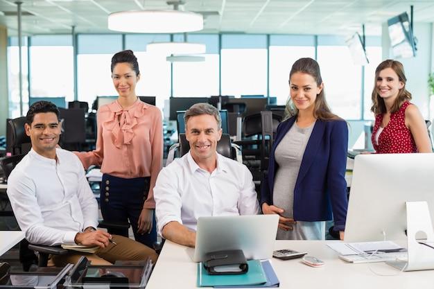 Compañeros de trabajo de pie juntos en un escritorio en la oficina