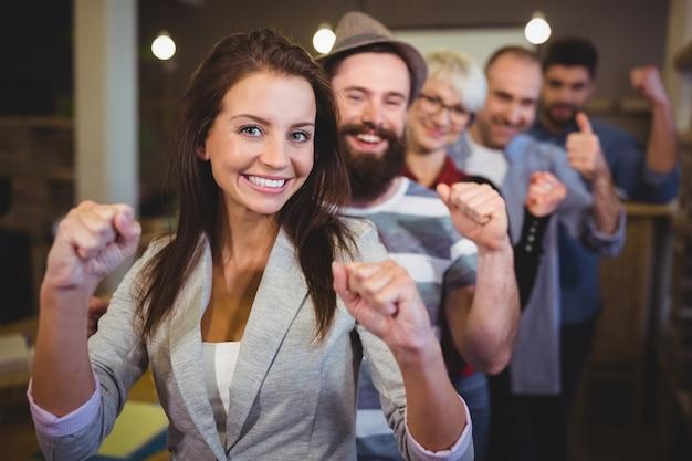 Compañeros de trabajo que animan con el puño cerrado en la oficina creativa