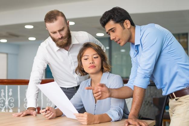 Compañeros de trabajo que ayudan al recién llegado a completar la solicitud de empleo