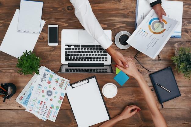 Compañeros de trabajo que comparten el mismo escritorio con un espacio de trabajo personalizado y trabajan con una computadora portátil y digital.