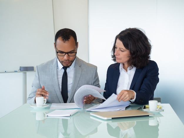 Compañeros de trabajo que comprueban el texto del acuerdo