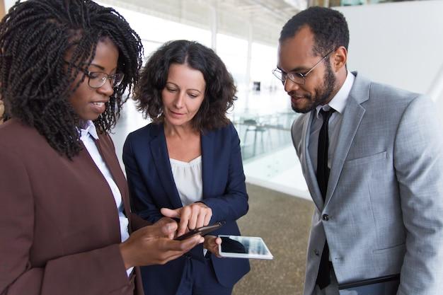 Compañeros de trabajo que consultan internet en dispositivos digitales