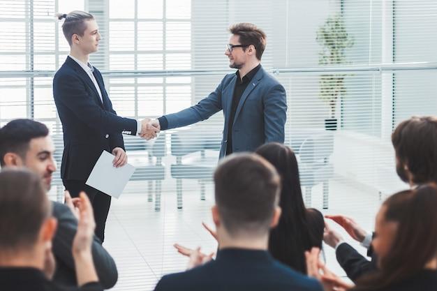 Compañeros de trabajo que se encuentran con un apretón de manos durante una reunión de grupo.