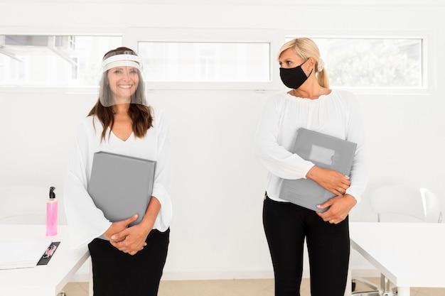 Compañeros de trabajo que mantienen la distancia social y usan protección facial