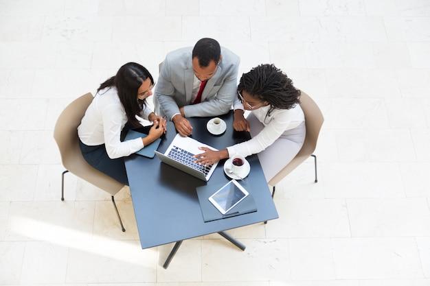 Compañeros de trabajo que miran contenido en la computadora portátil