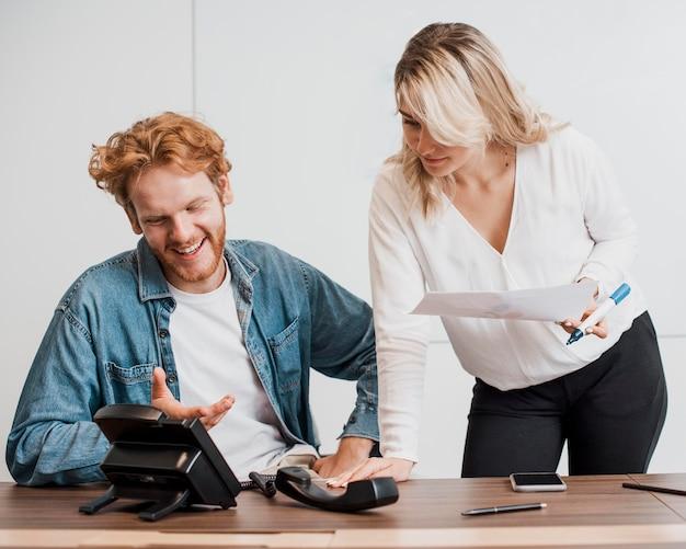 Compañeros de trabajo que tienen una conversación telefónica en el altavoz