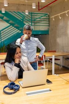 Compañeros de trabajo que tienen una conversación de trabajo mientras toman café negro